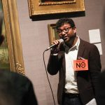 Rohit is speaking into a microphone in one of the galleries. He looks relaxed and confident. He is wearing a badge that says - End colonial anit queer laws - No 377! Defy the legacy of Babington Macaulay
