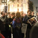 A photograph of members of audience holding placards from demonstrations. The main poster says No Going Back! There are about 10 people in the photo.
