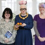 Photo portrait of Tracey holding her book Kitsch, Birdie holding two satsumas and Ruth not holding anything!