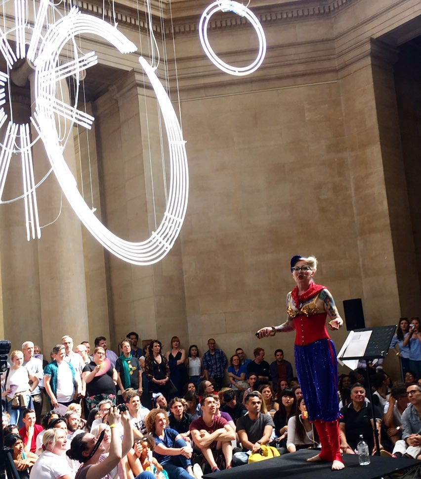 Bird holding forth on a podium in a large space in Tate Britain. She is wearing her Queer Communards red and blue outfit and is surrounded by the audience.