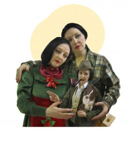 Well where to begin! This is a triptych of figures in the style of a Holy family. One figure is Birdie Allslop. Then Bird is dressed as a carpenter in a plaid shirt with a mallet in pocket. In the middle is an mini Birdie dressed as a posh farmer in a tweed hat and wax jacket. She is holding a cardboard cutout of a border collie. She is making a pointed gesture like a medieval painting.