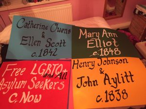 Four placards in bold colour from the rainbow flag. Each features the names of individual or groups of LGBTQI prisoners or detainees featured in the show.
