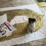 Trixie sits on an unfinished banner of Sam Fox. Sam is surronded by gold paint and is holding a copy of The Sun which says Lies! Lies! Lies! Lies! More fake news from The Scum!