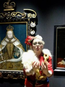 Bird in full rococo communist costume in front of the Queen Elizabeth 1 coronation portrait. Bird's hards are held imploringly to the camera