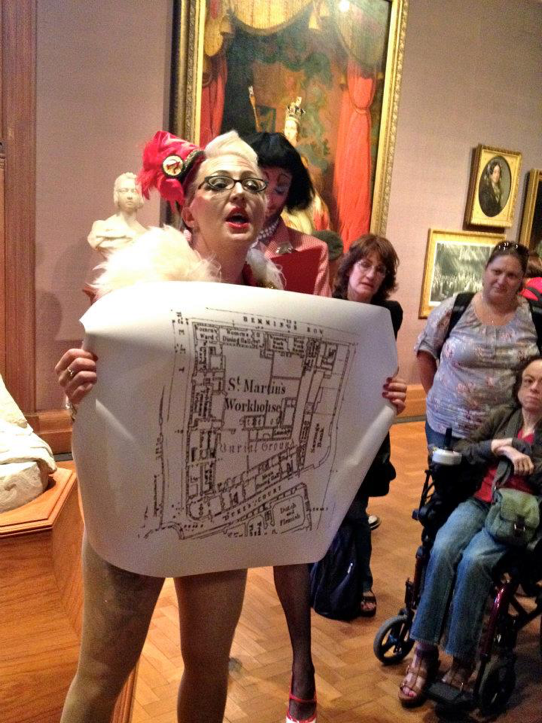 A photo from one of Bird's performances at the National Portrait Gallery. Bird is holding up a ground plan of St Martin's Workhouse. The audience is standing around her.