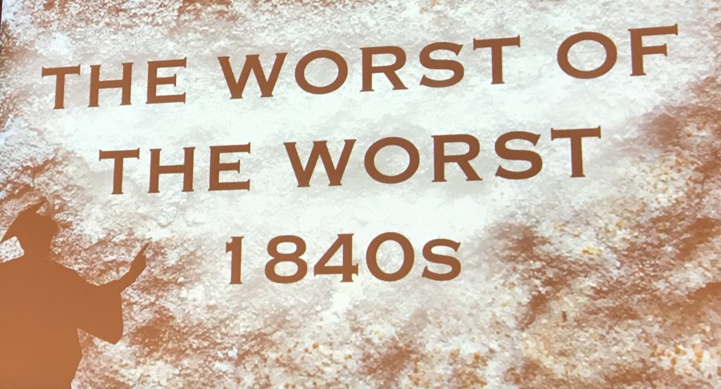 Bird's shadow in the corner of a projection of text 'The Worst of the Worst'