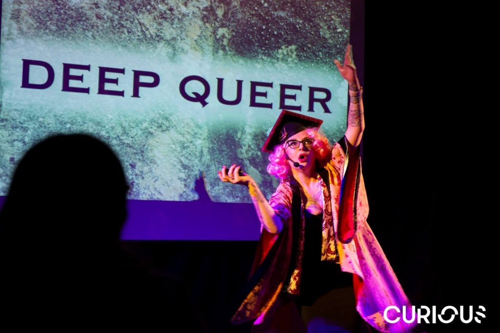 Bird on stage in front of text reading Deep Queer.